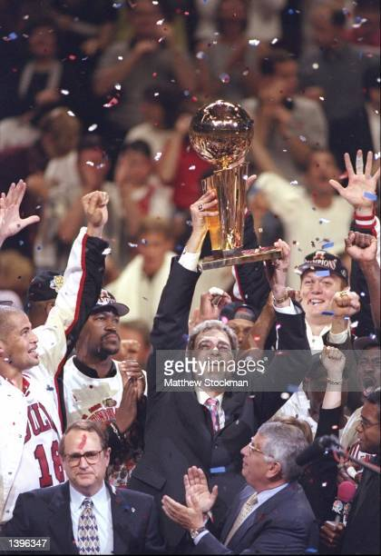 Brian Williams of the Chicago Bulls and team owner Jerry Reinsdorf look on as coach Phil Jackson holds up the trophy with NBA Commissioner David...
