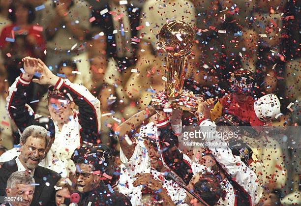 Chicago Bulls players celebrate with the trophy in a shower of confetti after winning game 6 of the 1997 NBA Finals at the United Center in Chicago...