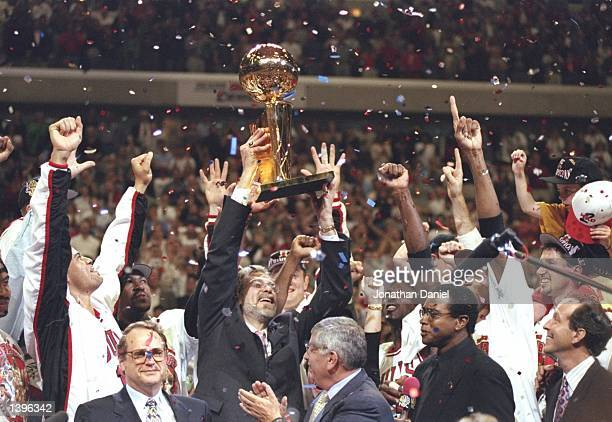 Coach Phil Jackson of the Chicago Bulls holds up the trophy as team owner Jerry Reinsdorf and NBA Commissioner David Stern look on after the Bulls...
