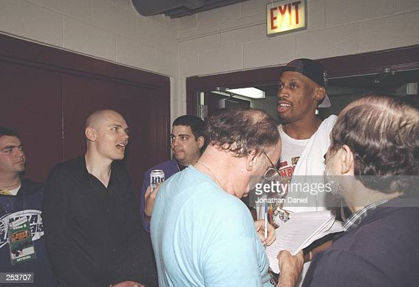 Dennis Rodman of the Chicago Bulls walks into the locker room with Billy Corgan of the rock group Smashing Pumpkins after the Bulls win game 6 of the...