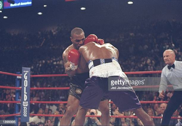 Evander Holyfield and Mike Tyson lock heads during their heavyweight title fight at the MGM Grand Garden in Las Vegas, Nevada. Holyfield won the...