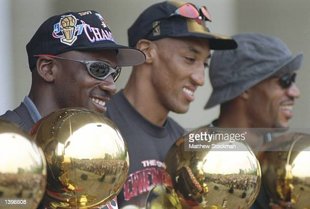 Guard Michael Jordan forward Scottie Pippen and forward Dennis Rodman of the Chicago Bulls look at their trophies during the Chicago Bulls Victory...