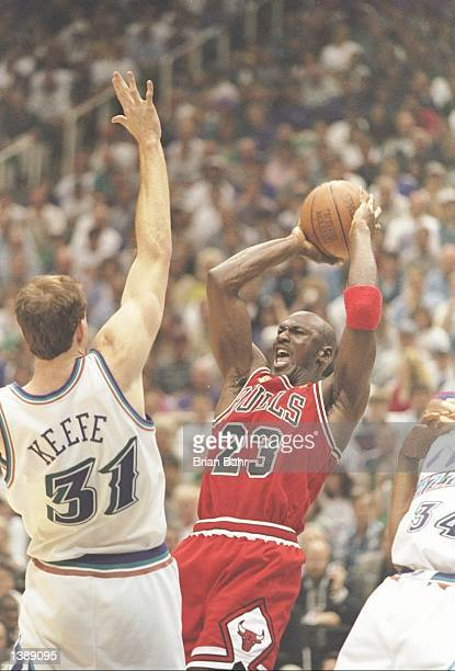 Guard Michael Jordan of the Chicago Bulls tries to fend off forward Adam Keefe of the Utah Jazz during a playoff game at the Delta Center in Salt...