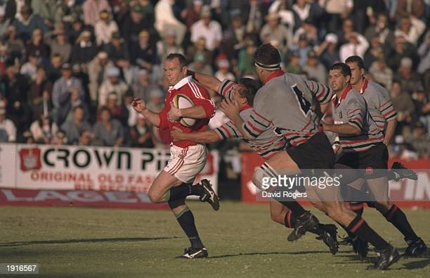 Ieuan Evans of the British Lions sprints away from the defence during the tour match against Mpumalanga at the Jan van Riebeeck Stadium at Witbank,...