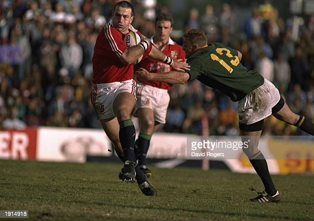 John Bentley of the British Lions goes past Percival Montgomery of the Emerging Springboks during the tour match in Wellington South Africa The...