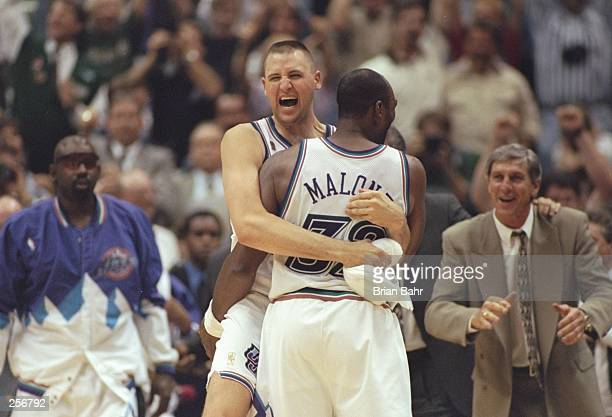 Karl Malone of the Utah Jazz celebrates with teammate Greg Ostertag as head coach Jerry Sloan looks on during the Jazz 7873 win over the Chicago...
