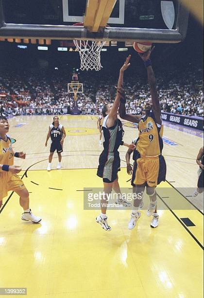 Lisa Leslie of the Los Angeles Sparks shoots the ball over Rebecca Lobo of the New York Liberty at the Great Western Forum in Inglewood California...