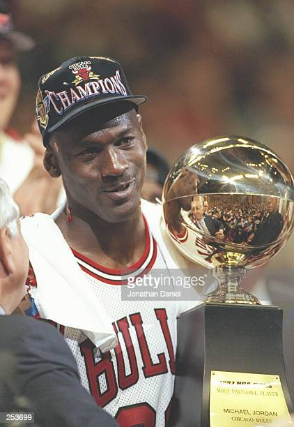Michael Jordan of the Chicago Bulls holds the 1998 NBA MVP trophy after the Bulls win game 6 of the 1997 NBA Finals at the United Center in Chicago...