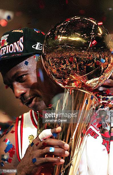 Michael Jordan of the Chicago Bulls holds the NBA Trophy after winning game six of the NBA Final against the Utah Jazz at the United Center in...