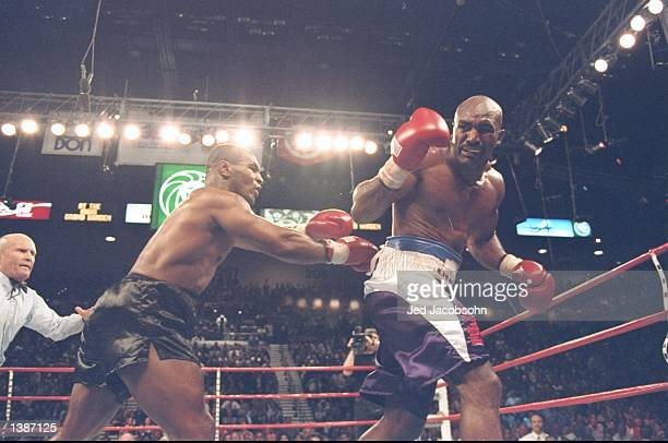Referee Mills Lane steps in as Mike Tyson pushes Evander Holyfield in the back after biting his ears in the third round of their World Heavweight...