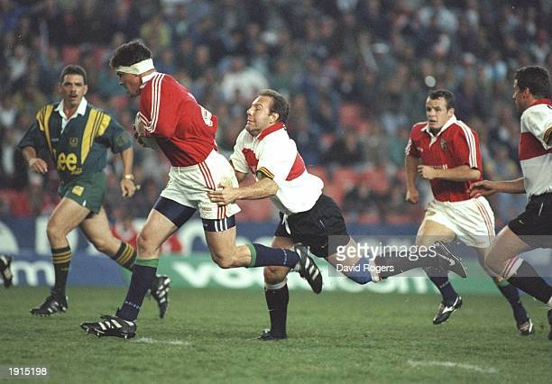 Rob Wainwright of the British Lions powers forward despite the tackle from Johan Roux of Gauteng during the tour match at Ellis Park in Johannesburg...