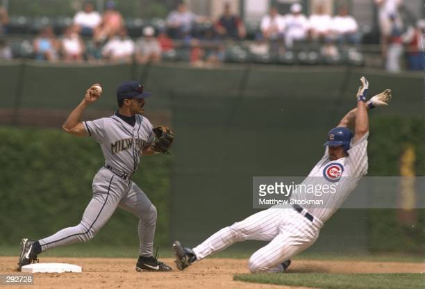 Runner Terry Mulholland of the Chicago Cubs slides into second base as infielder Jose Valentin of the Milwaukee Brewers turns a double play during...