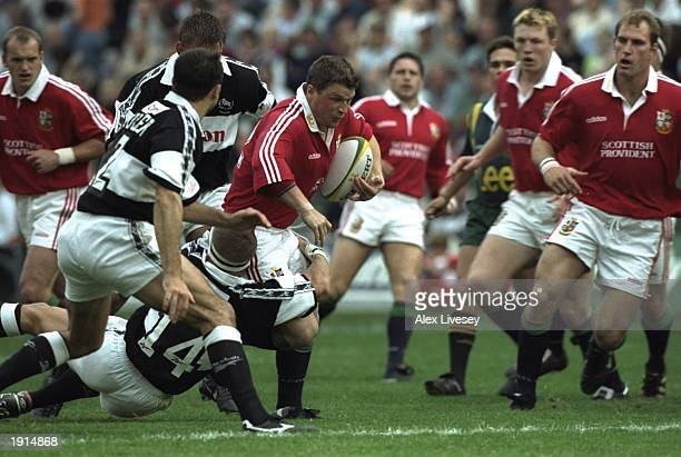 Scott Gibbs of the British Lions is tackled by Shaun Payne of Natal Sharks during the match at Kings Park in Durban Natal South Africa The British...