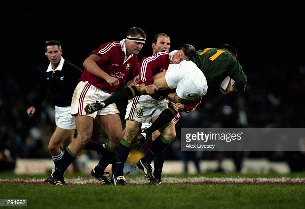 Scott Gibbs of the British Lions upends Andre Snyman of South Africa during the first Test Match at Newlands. The British Lions beat South Africa...