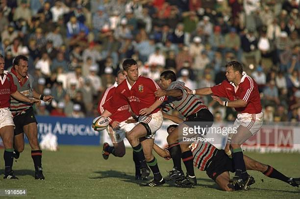 Will Greenwood of the British Lions passes to Nick Beal as he his tackled during the tour match against Mpumalanga at the Jan van Riebeeck Stadium at...