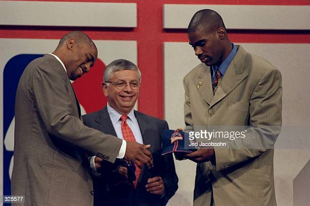 A picture of Vince Carter being traded to the Toronto Rapters and Antawn Jamison being traded to the Golden State Warriors in front of David Stern...