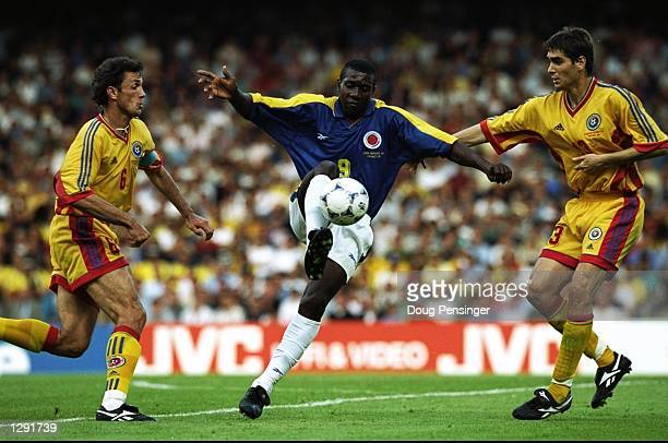 Adolfo Valencia of Colombia under pressure from Gheorghe Popescu and Liviu Ciobotariu of Romania during the World Cup group G game at the Stade...