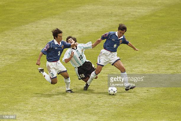 Ariel Ortega of Argentina goes down under pressure from Naoki Soma of Japan and team mate Motohiro Yamaguchi during the World Cup group H game at the...
