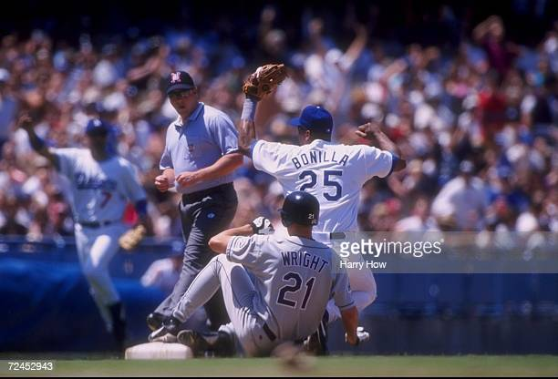 Bobby Bonilla of the Los Angeles Dodgers tags Jamey Wright of the Colorado Rockies out to complete a triple play during a game at Dodger Stadium in...