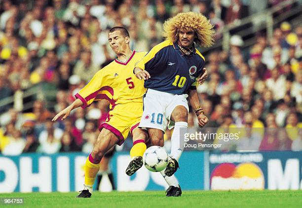 Carlos Valderrama of Colombia holds the ball up against Constantin Galca of Romania during the FIFA World Cup Finals 1998 Group G match played in...