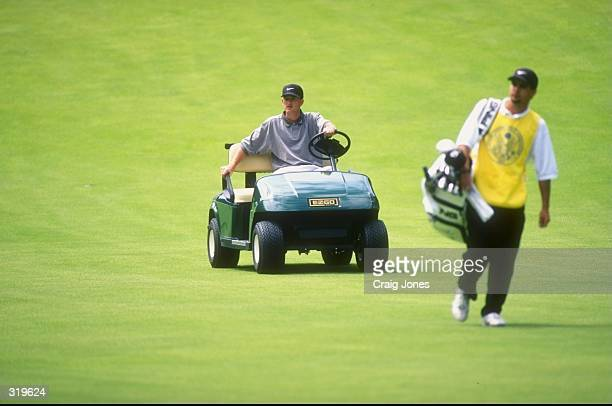 Casey Martin of the USA drives his golf cart as his caddie walks down the fairway during the 1998 US Open Championships on the 6797yard par70 Lake...