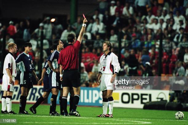 David Beckham of England is sent off by referee Kim Nielsen after lashing out at Diego Simeone of Argentina during the World Cup second round match...