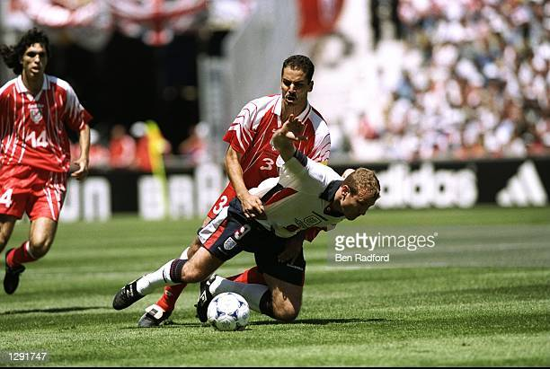 England captain Alan Shearer is brought down by Hatem Trabelsi of Tunisia during the World Cup group G game at the Stade Velodrome in Marseille...
