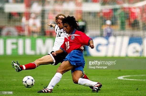 Fabian Estay of Chile is challenged by Roman Mahlich of Austria during the World Cup group B game at the Geoffroy Guichard Stadium in St Etienne...