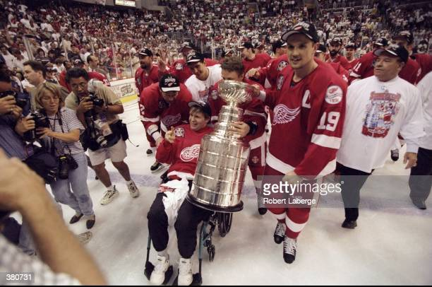 Former member of the Detroit Red Wing Vladimir Konstantinov poses with the Stanley cup and former teammates during the Stanley Cup Finals game...