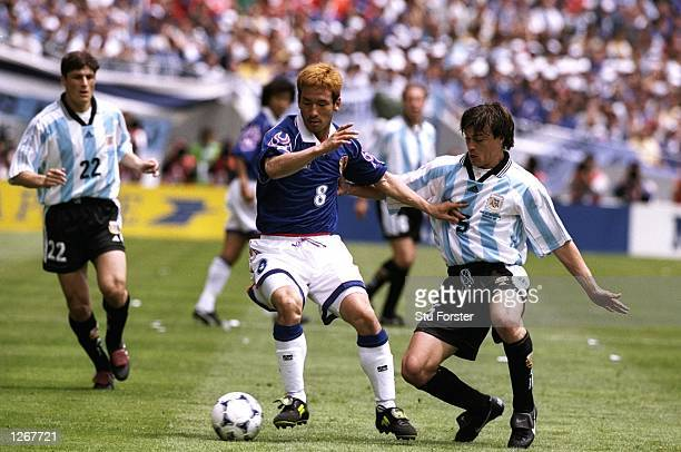Hidetoshi Nakata of Japan fends off Matias Almeyda of Argentina during the World Cup group H game at the Stade Municipal in Toulouse France Argentina...
