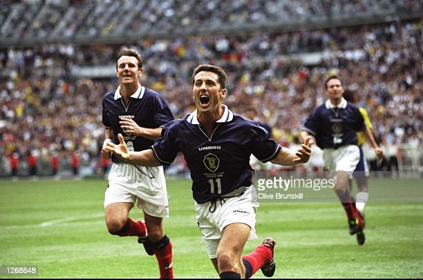 John Collins of Scotland celebrates after scoring from the penalty spot during the World Cup group A game against Brazil at the Stade de France in St...