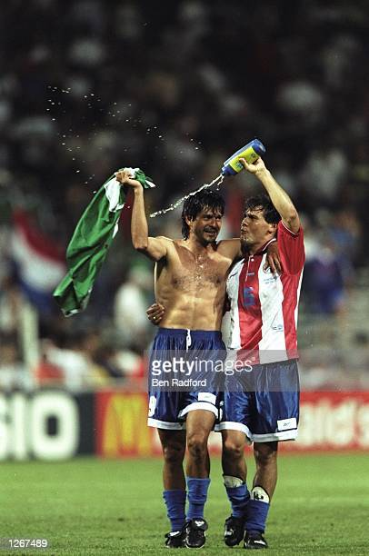 Jose Cardozo of Paraguay and team mate Celso Ayala celebrate qualifying for the knockout phase of the World Cup Finals after the group D game against...