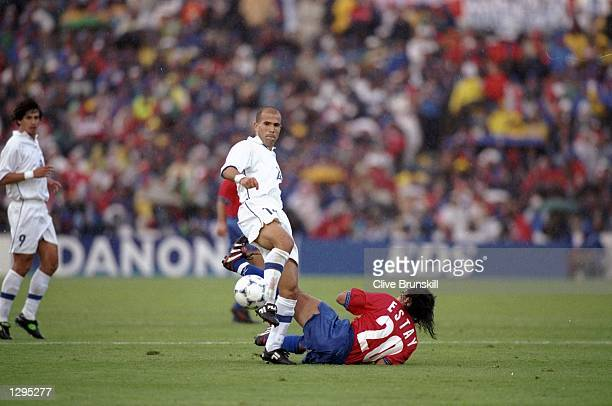 Luigi di Bagio of Italy is tackled by Chile's Fabien Estay in the match between Italy v Chile during the 1998 World Cup played in Bordeaux France...