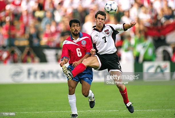 Mario Haas of Austria holds off Pedro Reyes of Chile during the World Cup group B game at the Geoffroy Guichard Stadium in St Etienne France The...