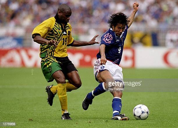 Masashi Nakayama of Japan takes on Frank Sinclair of Jamaica during the World Cup first round match at the Stade Gerland in Lyon France Jamaica won...