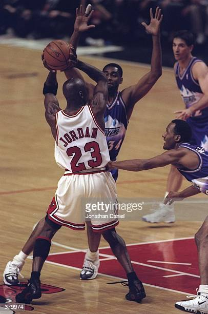 Michael Jordan of the Chicago Bulls in action against Chris Morris and Howard Eisley of the Utah Jazz during the NBA Finals Game 4 at the United...