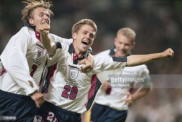 Michael Owen of England celebrates with team mate David Beckham after scoring in the World Cup group G game against Romania at the Stade Municipal in...