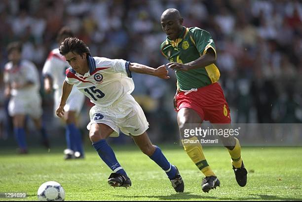 Moises Villarroel of Chile goes past Pierre Njanka of Cameroon during the World Cup group B game at the Stade de la Beaujoire in Nantes France The...