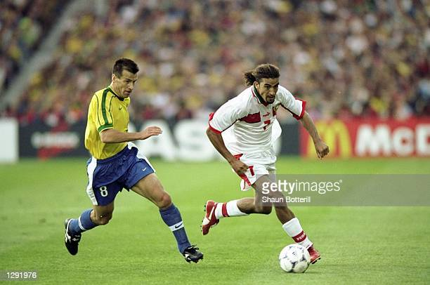 Moustafa Hadji of Morocco takes on Brazil captain Dunga during the World Cup group A game at the Stade de la Beaujoire in Nantes France Brazil won 30...