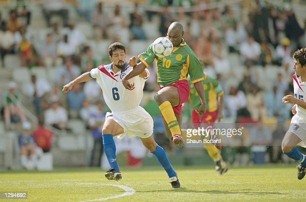 Patrick Mboma of Cameroon takes on Pedro Reyes of Chile during the World Cup group B game at the Stade de la Beaujoire in Nantes France Mboma scored...