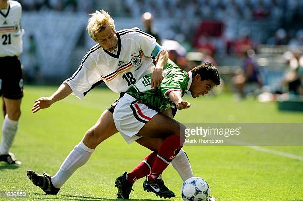 Pavel Pardo of Mexico holds off Jurgen Klinsmann of Germany during the World Cup second round match at the Stade de la Mosson in Montpellier France...