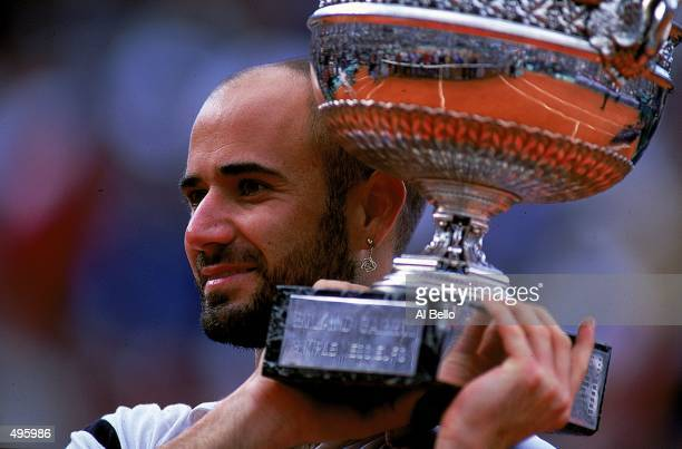 Andre Agassi of the USA holds up the trophy after defeating Andrei Medvedev of the Ukraine to win the men's singles final of the French Open at...