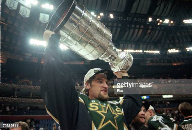 Captain Derian Hatcher of the Dallas Stars carries the Stanley Cup after the Stanley Cup Final game against the Buffalo Sabres at the Marine Midland...