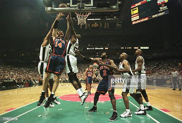 Chris Dudley of the New York Knicks gets hammered as he goes to the basket by Tim Duncan and David Robinson of the San Antonio Spurs during game two...