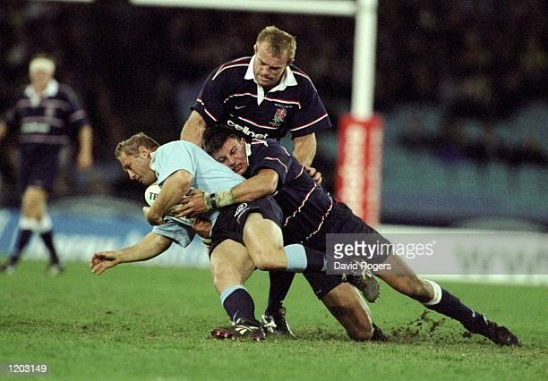 Dan Crowley of Australia is tackled by Martin Corry of England during the Centennary Test Match at Stadium Australia Homebush Sydney Australia The...