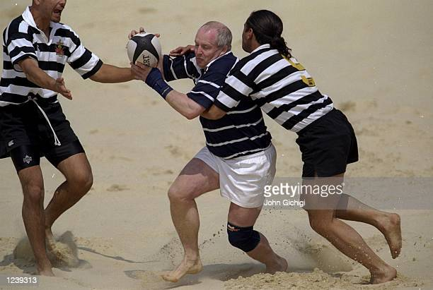 Ian Morrison of Scotland is tackled by Phil Edwards of New Zealand during the Beach Rugby Tournament held at the Richmond Athletic Ground London...