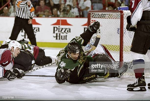 Jamie Langenbrunner of the Dallas Stars falls after he makes a goal as goalie Patrick Roy and Aaron Miller of the Colorado Avalanche lay on the ice...
