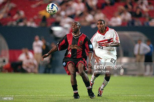 Adolfo Valencia of the New York/New Jersey MetroStars tries to get the ball before Eddie Pope of the D C United during the game at Giants Stadium in...