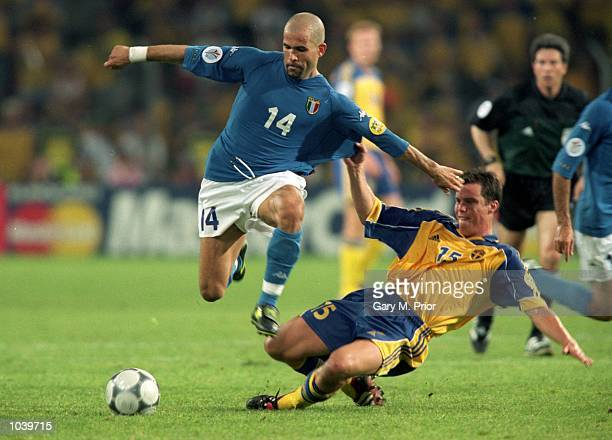 Luigi Di Biagio of Italy hurdles Daniel Andersson of Sweden during the European Championships 2000 group match at the Philips Stadium in Eindhoven...