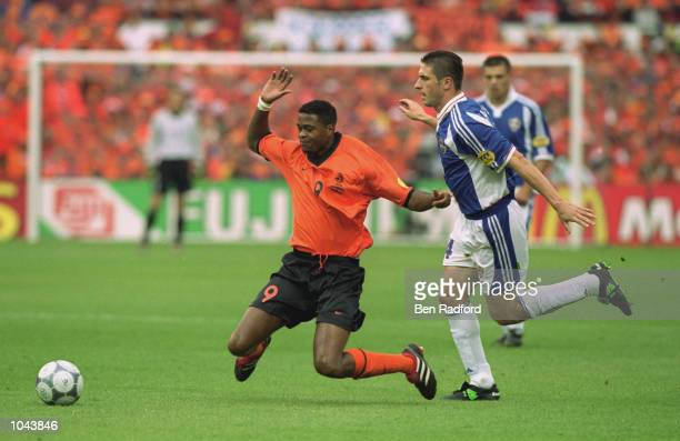 Patrick Kluivert of Holland is felled by Nisa Saveljic of Yugoslavia during the European Championships 2000 quarter-final at the De Kuip Stadium in...